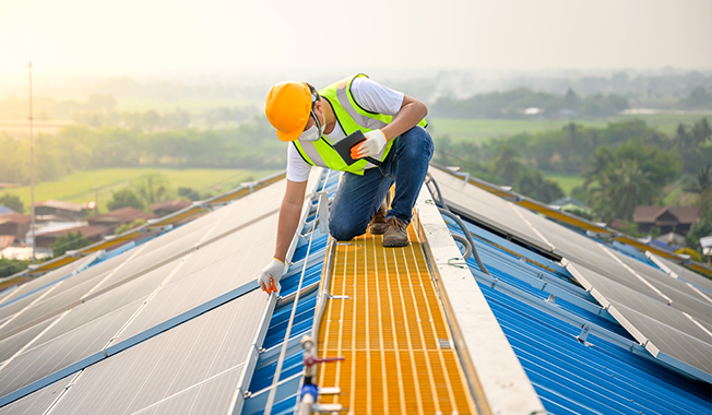 Man working on roof with solar panels to combat climate change.