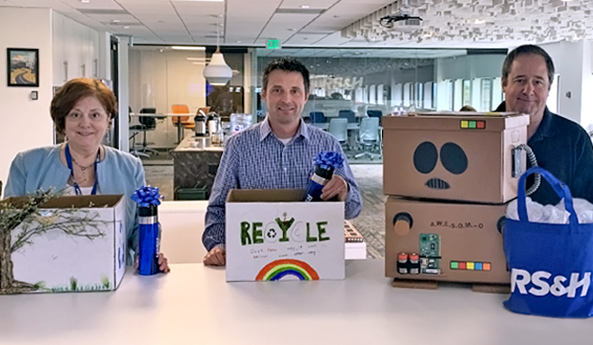 RS&H's Certifiably Green Denver office associates displaying their decorated recycle boxes.
