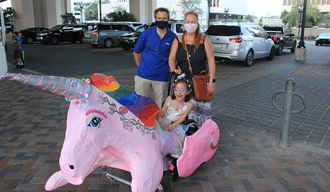 A young girl rides in a unicorn wheelchair-accessible Halloween costume at the community involvement event.