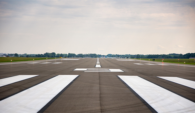 Close up of a runway with the lines to guide the pilots flying in.