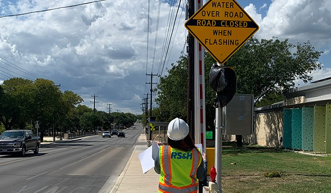 RS&H employee inspecting high water detection (HALT) system in Bexar County, Texas to notify motorists of flash floods.