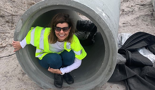 Construction Management's Susan Lake sitting in a culvert on a transportation infrastructure site.
